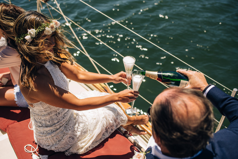 couple celebrating their wedding drinking champagne on a boat