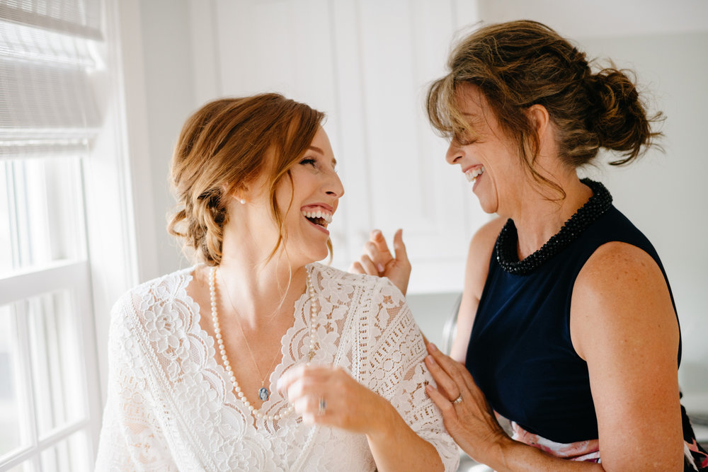 bride laughing with her mom getting ready in nantucket wedding