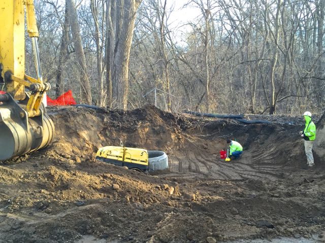 After completing work on the sewer system and installing an access manhole shaft, the crew used a remote controlled trench roller to firmly compact the soil with vibrations and pressure.