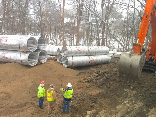 An extensive stormwater management system is being installed on the east side of the church. It will store runoff from both parking lots and the building, and release it gradually for filtration through the woods below.