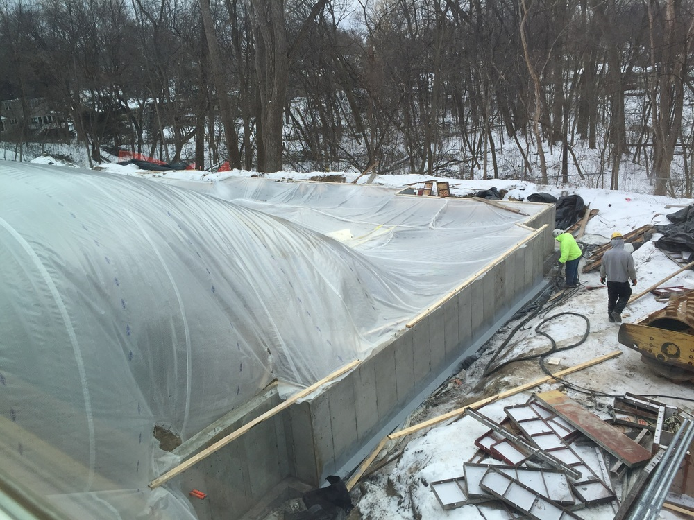 While a makeshift tent protects the interior of the south addition, the exterior of the foundation walls gets a weatherproofing treatment.