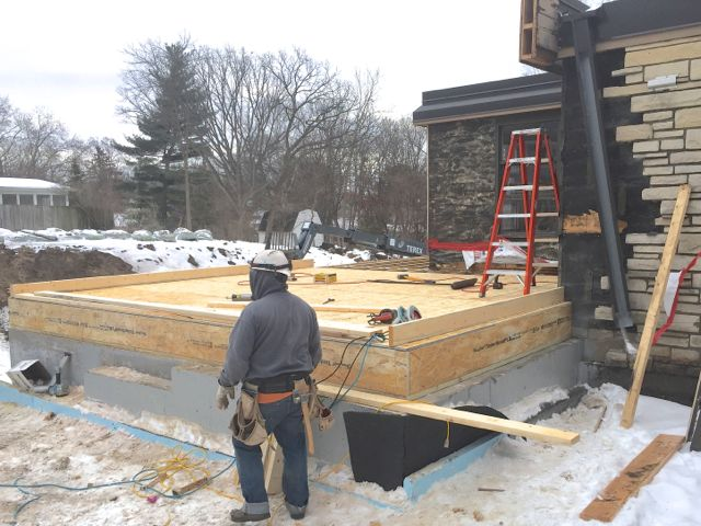 First, a floor is built on the foundation of the new kitchen addition.