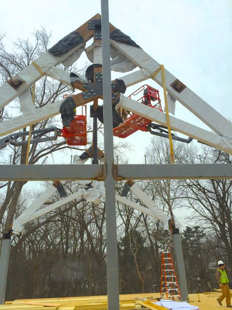 The first two trusses for the new sanctuary ceiling have been lowered in place by a crane, and connected with a giant cross beam.