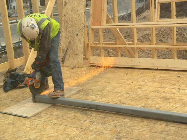 Sparks fly as an iron worker cuts a steel support to the proper length.