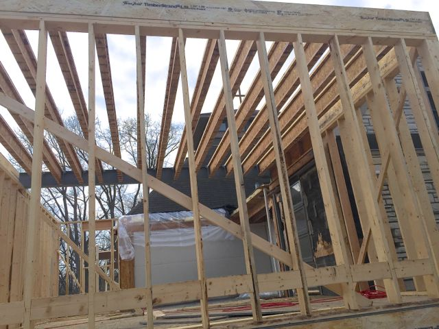 A large steel beam spanning the top of kitchen addition was anchored inside the existing building to provide extra stability. Wood ceiling joists are now being added between the center beam and outer walls.