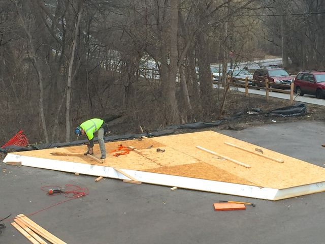 The structural insulated panels (SIPs) for the roof had to be delivered in pieces in order to fit on a truck bed.  (See photo from the 03/14/16 blog post.)  Workers are now busy pre-assembling them into unified panels for each section of the roof. The plans below show how the different components need to be joined together.