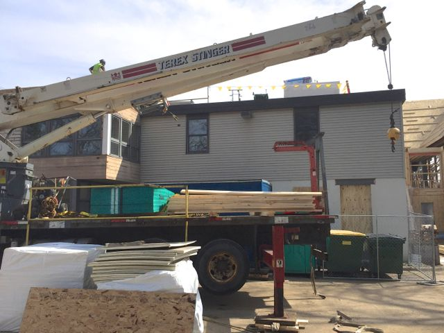 Work is underway to replace our problematic flat roof. Improvements include adding several inches of insulation, increasing the slope to reduce standing water, and switching the tar and gravel built-up section to an EPDM rubber roof system. Pictured above is the crane used to lift pallets of roofing supplies into position.