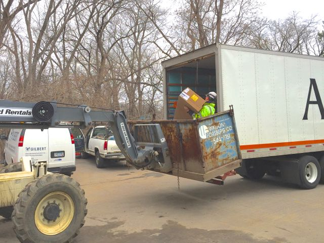 A few windows at a time are taken from the delivery truck and placed in a lift bucket. They are then driven to their approximate installation location and unloaded by the construction crew.