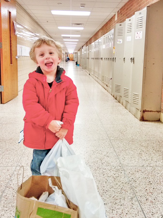 "3-year-old Luke is excited to help deliver groceries to the ""big kids"" at Highlands Elementary School."