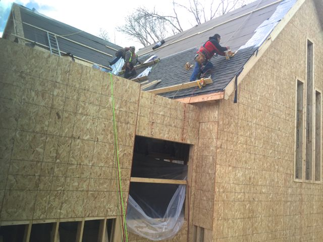 In between bouts of rain and snow, roofers plug away at shingling the roof of the new sanctuary.