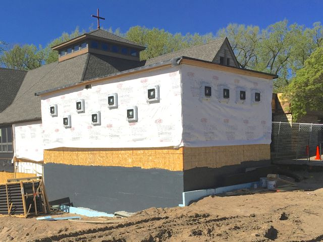 All of the kitchen addition windows have been installed. The foundation is being waterproofed, and the wood walls are getting covered with a vapor barrier wrap. Soon, the exterior will be ready for the installation of stone facing.