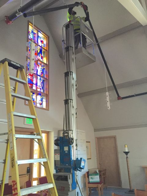 Safety in our facility is being enhanced by the installation of a sprinkler system in both the old and new sections of the building. Above, a worker is shown connecting new water pipes in the existing sanctuary. In a few months, this space will be transformed into a fellowship hall.