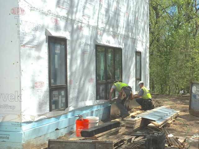 After insulating and wrapping the exterior of the south addition, crews then installed flashing along the base of the walls (pictured above). Now, the process of putting on the fiber cement siding is underway. Although all of it will be painted the same color, alternating sections with lap siding (shown below) and shingle siding will provide textural variation.