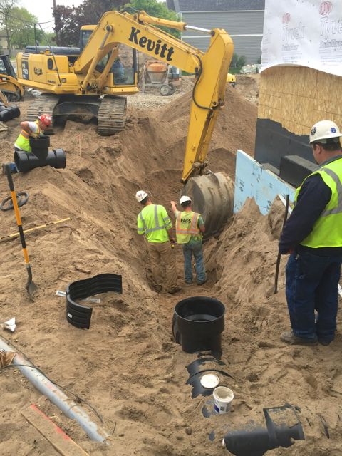 A network of underground pipes is being installed to funnel water runoff from rooftop scuppers and ground level drains into the large collection tanks that were buried in January.