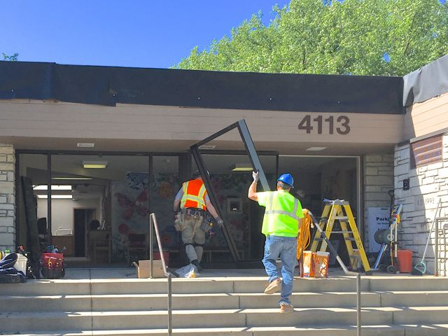 Today, workers are replacing the glass walls and doors in the front entryway with more energy efficient units. The new doors will be shifted eastward, and later in the project an inner vestibule will be added to control the loss of heat/cooling.