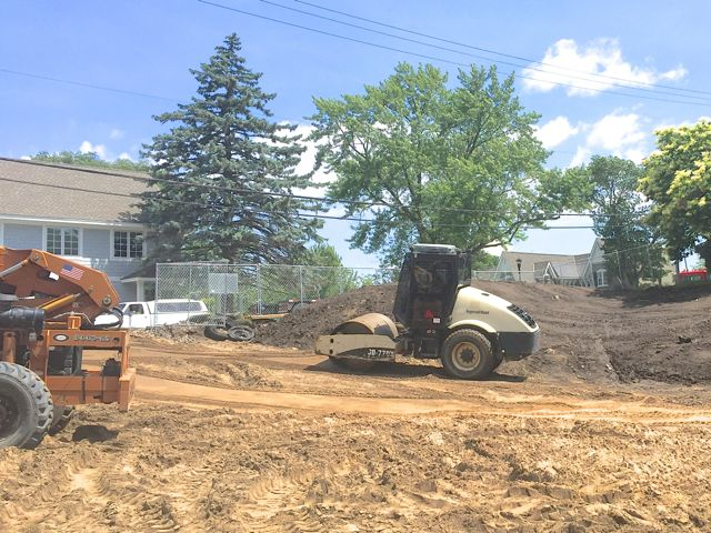 With most of the east side grading complete, work can begin on creating a stable base for the new parking lot. Today, a roller started compacting soil to smooth out the driveway area.