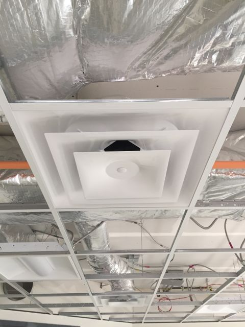 After the ceiling grid was installed in the lower level classrooms, crews added troffers (recessed light fixtures) and connected vents to HVAC ductwork.