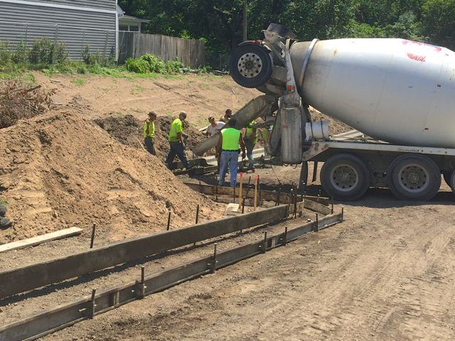After compacting the soil in the east parking lot and and laying out forms around the perimeter, today crews began pouring cement for curbs.