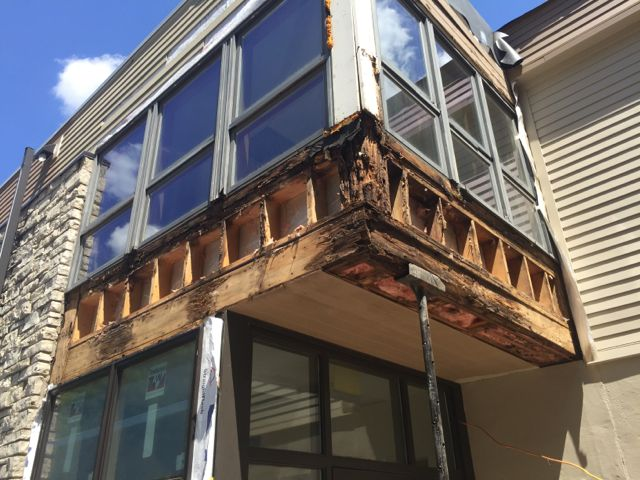 A few days ago, extensive damage was uncovered around and under the west window nook, with chunks of wood crumbling away when old siding was removed. Crews braced the structure up for safety, and replaced the rotted sections with sturdy new framing and beams. The installation of fiber cement siding will follow the addition of fresh insulation, Tyvek moisture barrier wrap, and brand new windows, making the space as good–and safe–as new.