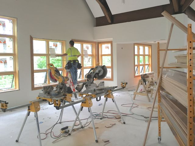 Finish carpenters are hard at work installing wood trim on one side of the new sanctuary, while wood flooring goes in across the room. Above it all, electricians are almost finished with the lighting system.
