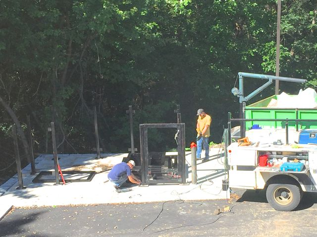 Workers are constructing a screened enclosure that will keep our trash and recycling dumpsters close at hand, and out of sight.