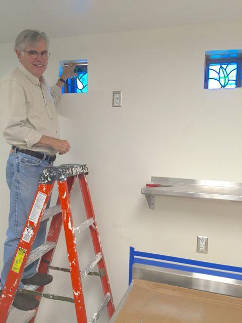 Today, artist and ECLC member Dan Mason installed the stained glass windows that he created for our kitchen. Fittingly enough, food is the unifying theme for the series of images, which includes the loaf of bread and fish pictured below.