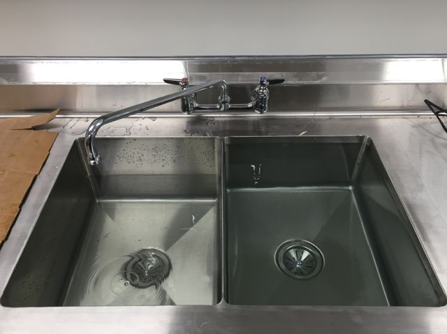 With the kitchen counters and sinks all in place, the plumbing crew was able to test the caulking, seals, and pipe fittings for leaks. Everything passed with flying colors, including the food prep sink pictured above.