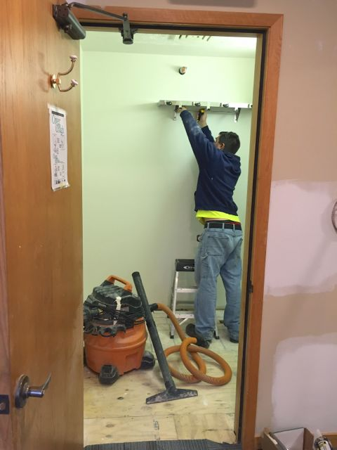 Workers are continuing the transformation of the old northwest bathroom into a janitor closet to service the upper level.