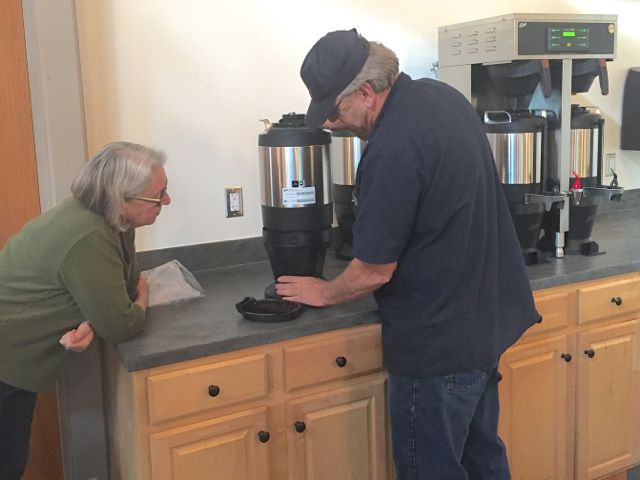 Karen Boyum, Hospitality Team Coordinator, listens intently as a technician explains how to operate and maintain ECLC's new coffee brewer and water filtration system.