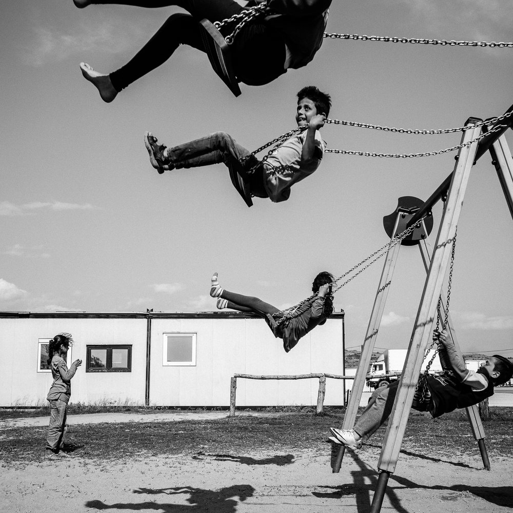 Children playing on a playground in Nea Kavali Camp, Greece, 2016