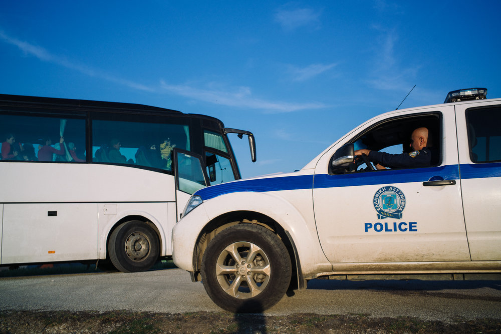A Greek police escorts a bus full of asylum seekers who are being transported to official camps run by the government.