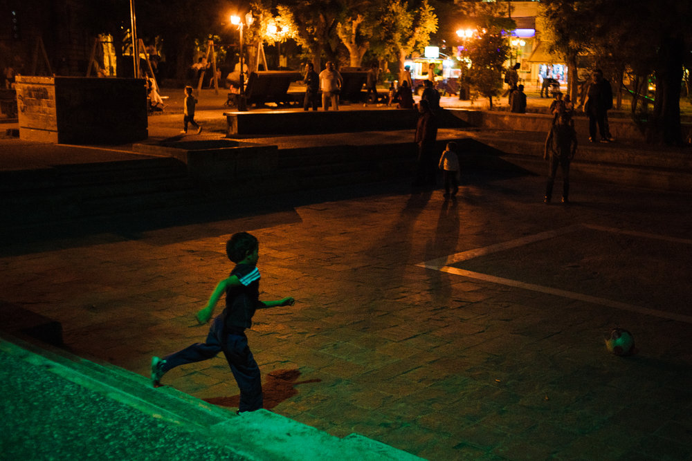 A Syrian boy plays football in the public playground late at night, after all the locals have left. The asylum seekers still face prejudice from a minority of the locals and fearing discrimination, they inhabit the social spaces after the locals have gone.