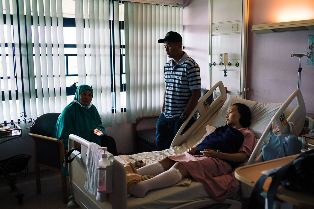 Hidayah (R), Raihan (M), and Hidayah's mother (L), looked on in despair after confirming with the doctors that there might be something wrong with the baby.  She was unresponsive and unconscious ever since she was born.