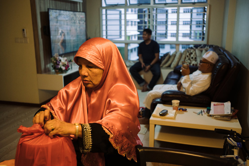 Hidayah's mother (foreground) and father (background, in white) tried their best to provide support for their daughter in every possible way.  Here, the preparation for a prayer dedicated to Hana is underway at Hidayah's apartment.