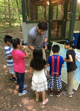 Avian and Research Technician, Eliot Berz,             teaching a young group about bird migration.
