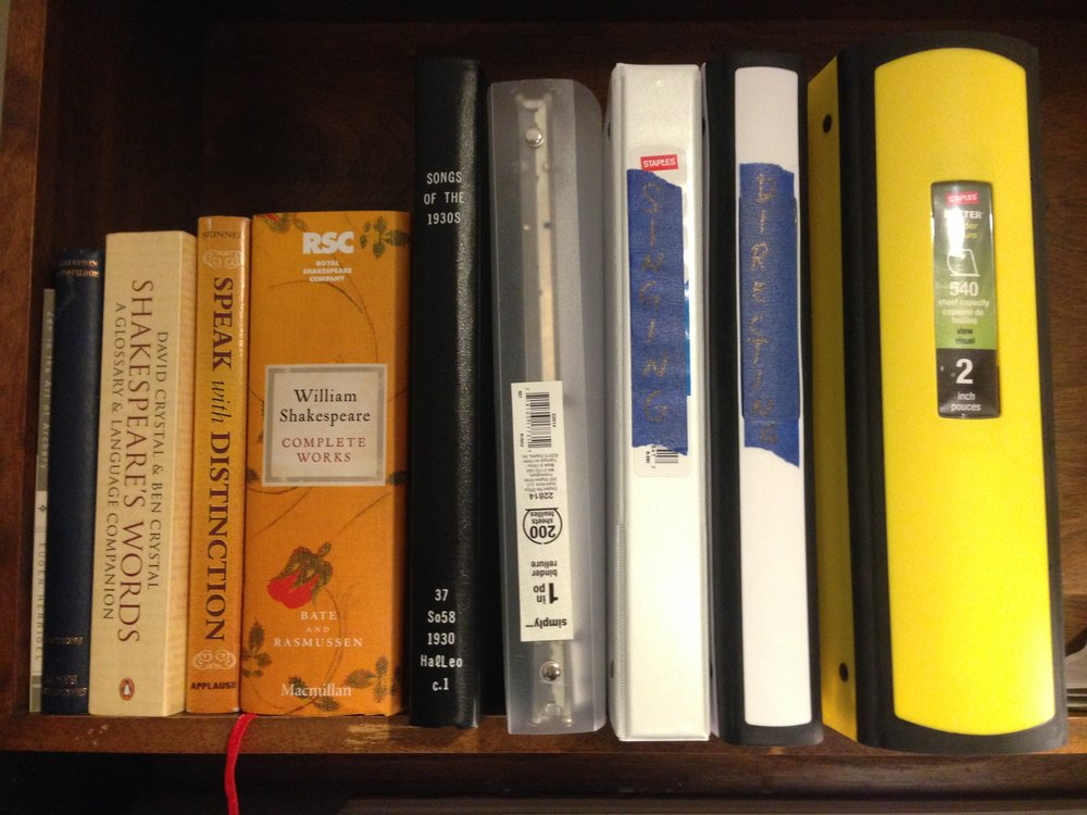 A typical Juilliard drama student's shelf contains a Shakespeare Glossary, a Shakespeare Anthology, a speech book, and binders for various readings.