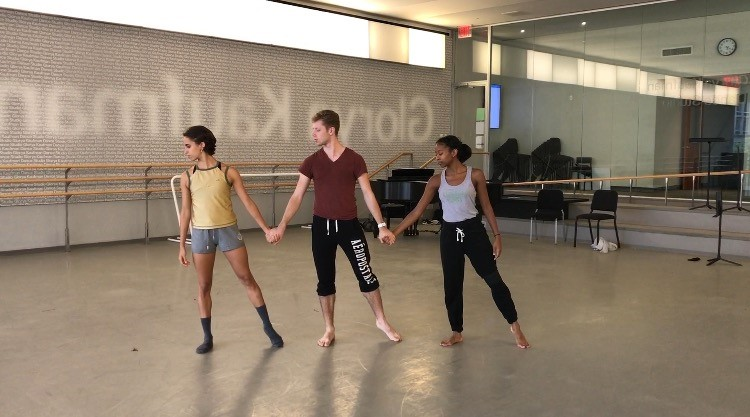 Photo of second year dancers Lúa Mayenco, Alexander Sargent, and Naya Lovell preparing to rehearse a section of ChoreoComp.