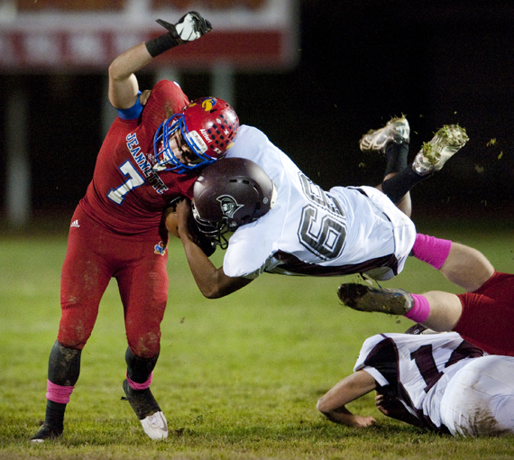 Jeannette's Zack Altieri rushes around Greensburg Central Catholic's Killian Joseph on Friday, Oct. 24, 2014 at McKee Stadium in Jeannette. Jeannette won 36-0.