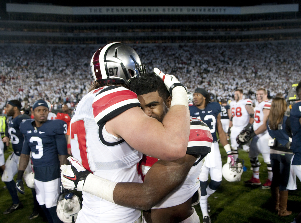 Ohio State running back Ezekiel Elliott (15) receives a hug from Ohio State defensive lineman Joey Bosa (97) after Bosa sacked Penn State quarterback Christian Hackenberg (14) on the last play of the game at Beaver Stadium on Oct. 25, 2014, in University Park. Ohio State won 31-24.