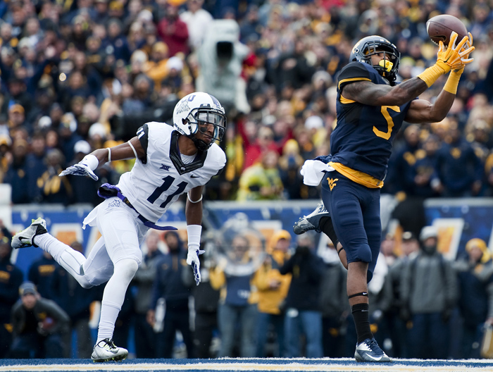West Virginia wide receiver Mario Alford (5) catches a touchdown pass over TCU cornerback Ranthony Texada (11) on Saturday, Nov. 1, 2014 in Morgantown, W.Va. TCU won 31-30.