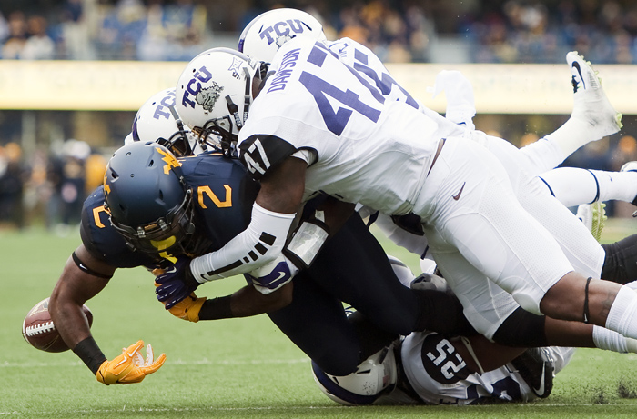 West Virginia running back Dreamius Smith (2) loses the ball while tackled by a host of TCU defenders on Saturday, Nov. 1, 2014 in Morgantown, W.Va. TCU won 31-30.
