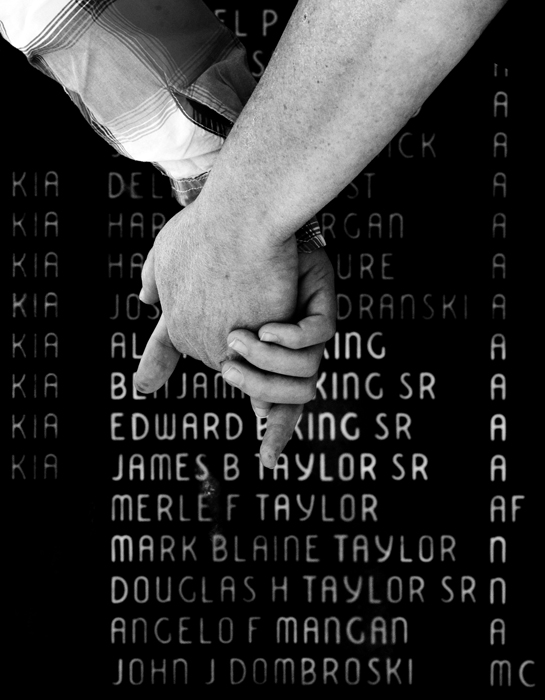 Elizabeth Kiliany, 13, holds the hand of her mother Jane Loughran while they search for the names of Kiliany's great uncles of the Stella family at Veterans Park in Mt. Pleasant on Veterans Day Tuesday, Nov. 11, 2014. Both are from Greensburg.