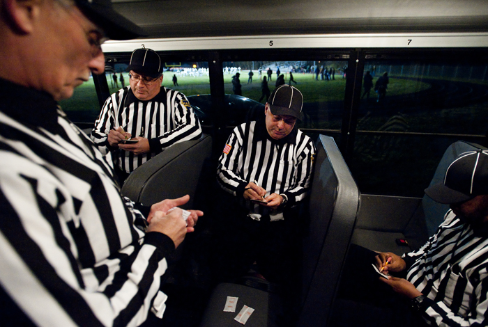 From left to right, officials Larry Hoover, Gary Heinrich, Tim Layton and James Matthews prepare their notes inside a school bus as they stay warm before the Blairsville and Portage District 6 semifinal game on Saturday, Nov. 15, 2014 in Blairsville. Portage won 28-24.