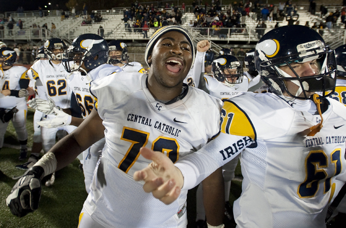 Central Catholic's C.J. Thorpe (73) and Patrick Phibbs (61) celebrate their win as time expires against Penn-Trafford on Friday, Nov. 14, 2014 at Norwin High School. Central Catholic won 52-34.