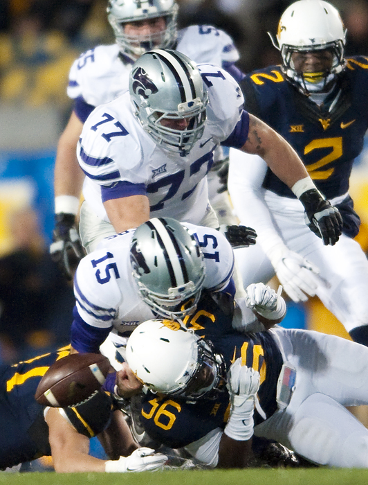West Virginia linebacker Shaq Petteway (36) dislodges the ball from Kansas State quarterback Jake Waters (15) at Milan Puskar Stadium on Thursday, Nov. 20, 2014 in Morgantown, W.Va. Kansas State won 26-20.
