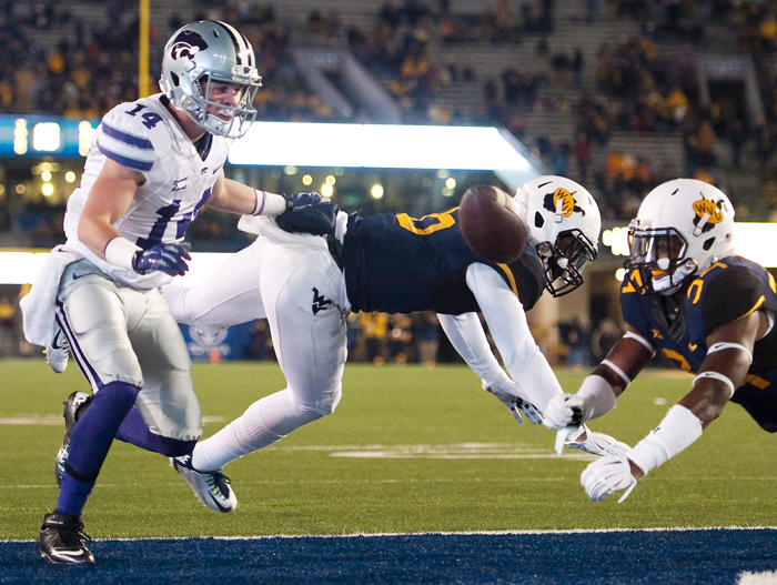 Kansas State wide receiver Curry Sexton (14) is pressured by West Virginia safety Dravon Henry (6) and West Virginia cornerback Ishmael Banks (34) at Milan Puskar Stadium on Thursday, Nov. 20, 2014 in Morgantown, W.Va. Kansas State won 26-20.