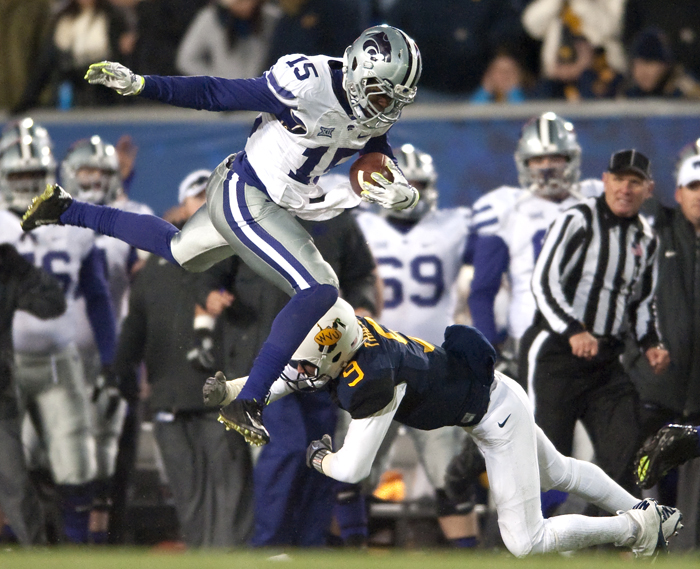 Kansas State defensive back Randall Evans (15) hurdles West Virginia quarterback Clint Trickett (9) after an interception at Milan Puskar Stadium on Thursday, Nov. 20, 2014 in Morgantown, W.Va.