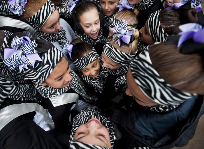 Sasha Hoffman, 7, of Hempfield with Dancers by Design (middle) huddles with her fellow dancers to keep warm before the City of Greensburg Holiday Parade on Saturday, Nov. 22, 2014.