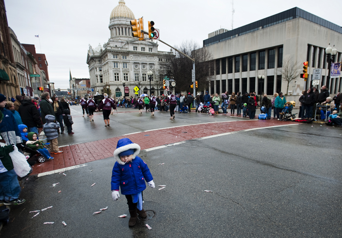 Maizey Hume, 3, of Boise, Idaho eats one of the many lollipops around her on Main Street during the City of Greensburg Holiday Parade on Saturday, Nov. 22, 2014.