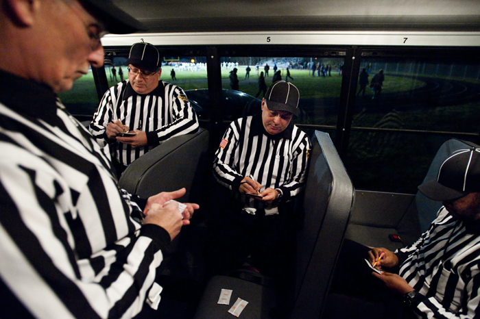 From left to right, officials Larry Hoover, Gary Heinrich, Tim Layton and James Matthews prepare their notes inside a school bus as they stay warm before the Blairsville and Portage PIAA playoff game on Saturday, Nov. 15, 2014 in Blairsville.